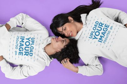 Hoodie Mockup Featuring Two Women Lying on a Flat Surface Looking at Each Other 30405
