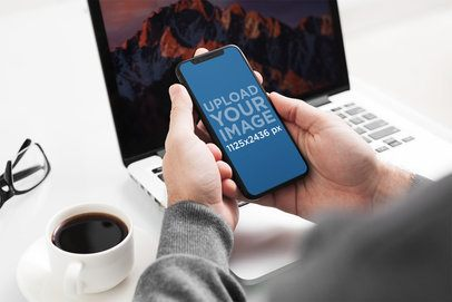 Mockup of a Man Using His iPhone 11 Pro in Front of His Office Desk 2151-el1