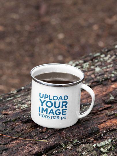 Mockup of a 12 oz Enamel Mug with a Silver Rim Placed on a Fallen Tree 30820
