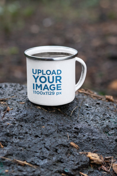 Mockup Featuring a 12 oz Enamel Mug with a Silver Rim Placed on a Rock 30822a