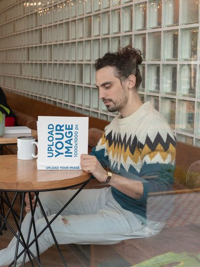 Square Book Mockup Fearing a Man Reading at a Cafe 30916