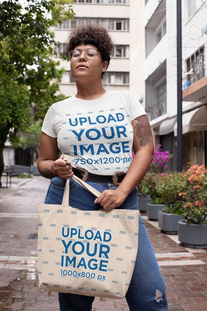 Mockup Featuring a Tattooed Woman in a Plus Size T-Shirt Holding a Tote Bag on the Street 30891