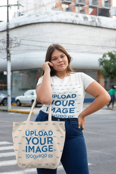 Mockup of a Woman with a Plus Size T-Shirt Holding a Tote Bag on the Street 30966
