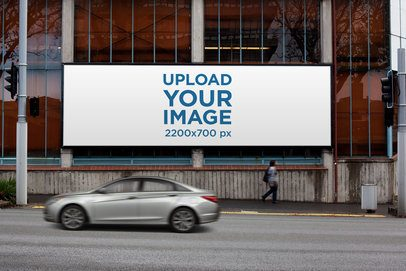 Mockup of a Billboard Placed on a Glass Building by a Street 2880-el1