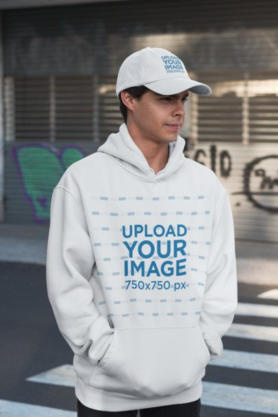 Hoodie Mockup of a Young Man Wearing a Dad Hat in an Urban Setting 31178