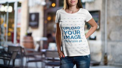 Mockup of a Woman Wearing a T-Shirt with a Restaurant in the Background 2990-el1