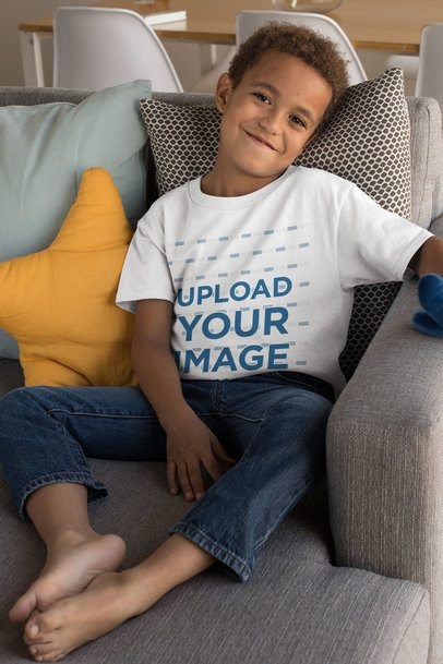 T-Shirt Mockup Featuring a Smiling Kid Sitting on a Couch 31639