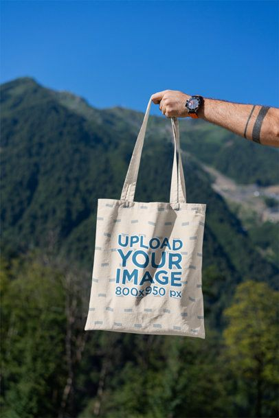 Mockup Featuring a Man's Hand Holding a Tote Bag Against a Natural Scenery 3131-el1