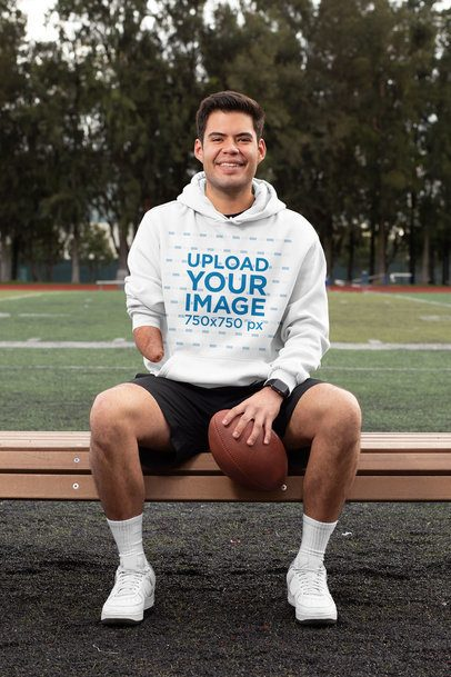 Hoodie Mockup of a Happy Man Sitting on the Bench of a Football Field 32497