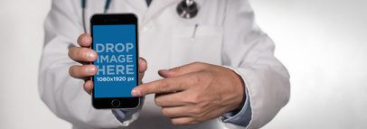 Black iPhone Plus Mockup Held in Frontal View by a Male Doctor a12403