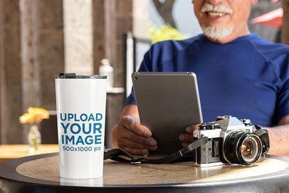 Travel Mug Mockup Featuring a Man Reading at a Coffee Store 32893