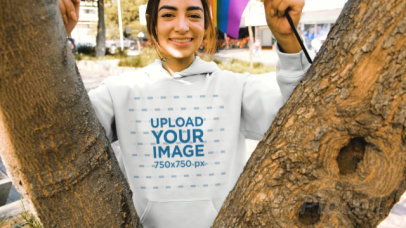 Pullover Hoodie Video Featuring a Happy Woman Holding a Small LGBT Pride Flag by a Tree 33375