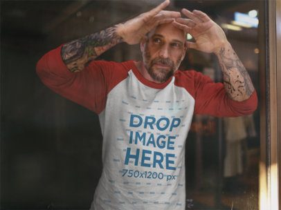 Man Wearing a Raglan Tee While Looking Out a Window Mockup a12609a