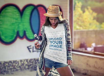 Mockup of a Woman Wearing a V-Neck T-Shirt and Holding a Vintage Camera 3687-el1