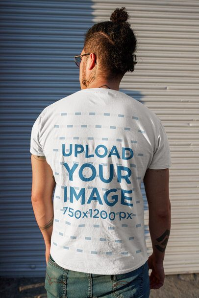 Back View T-Shirt Mockup Featuring a Man With a Head Bun Standing on the Street 32814