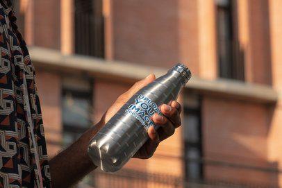 Mockup of a Man Holding a Sublimated Aluminum Bottle Outside 33503