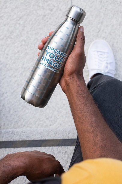 Mockup of a Man Holding an Aluminum Bottle in His Hand 33522
