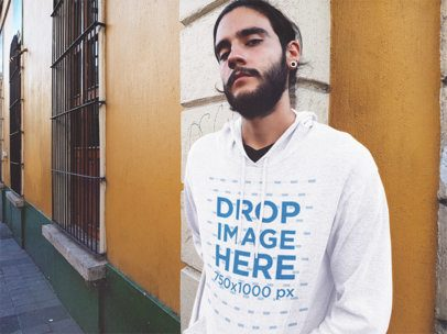 Young Hipster Guy with a Beard Wearing a Pullover Hoodie Mockup While Leaning on a Yellow Wall a12623