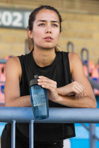 Mockup of a Woman Holding a Bike Bottle While Watching a Sports Match 33506