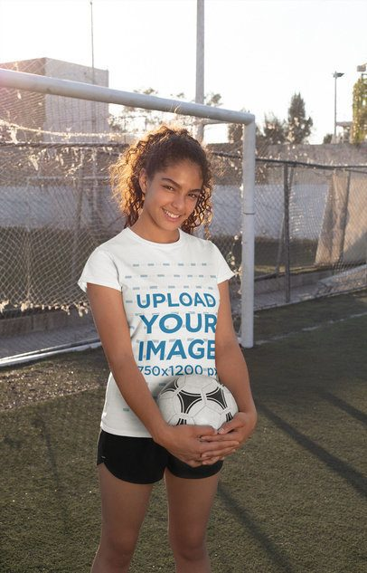 Tee Mockup of a Smiling Teenager Holding a Soccer Ball in the Field 33561