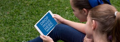 Two Girls Playing with a White iPad Mini Mockup in Landscape Position in their Garden a13002wide
