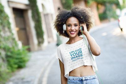 Mockup of a Woman with a Crop Top Tee Listening to Music on the Street 34035-r-el2