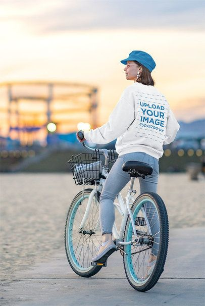 Mockup of a Young Woman with a Crewneck Sweatshirt Riding a Bike Outside 34159-r-el2