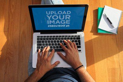 MacBook Pro Mockup of a Man Sitting on the Floor 36701-r-el2