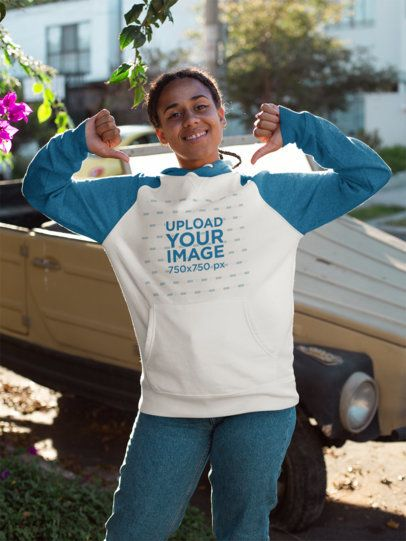Mockup of a Woman on the Street Pointing at Her Raglan Hoodie 24167
