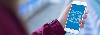 Mockup Template Of a Woman's Hand Holding an iPhone at a Stadium a14090wide