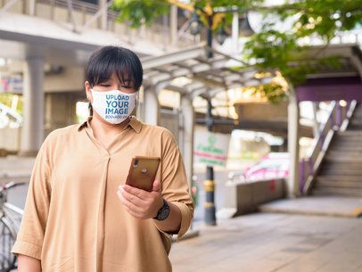 Face Mask Mockup of a Woman Checking Up Her Phone in the Street 41630-r-el2