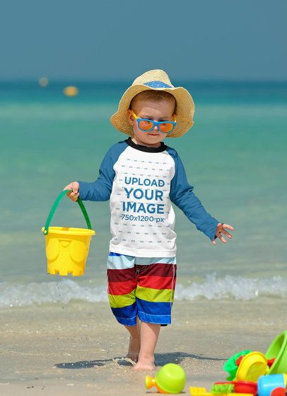 Mockup of a Baby Wearing a Raglan Long Sleeve Tee at the Beach 42127-r-el2