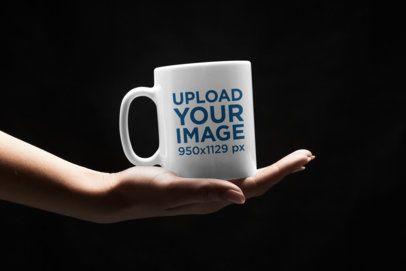 Mockup of a Woman Holding an 11 oz Mug in the Dark 43539-r-el2