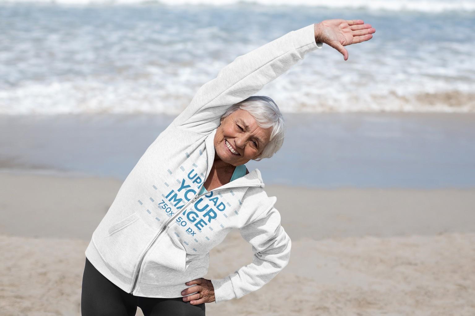 Full-Zip Hoodie Mockup of a Senior Woman Working Out at the Beach 42634-r-el2