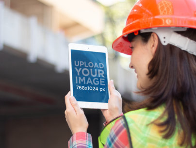 Mockup of a Woman Holding an iPad at a Construction Site 12572a