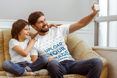 T-Shirt Mockup Featuring a Dad and His Son Sitting on a Couch and Taking a Selfie 44917-r-el2