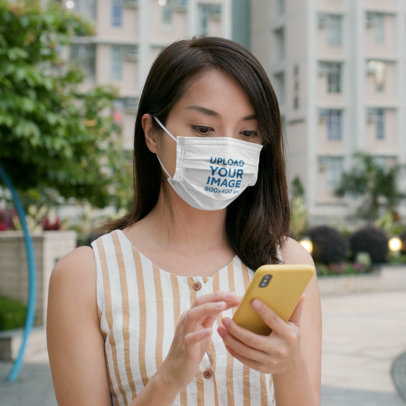 Face Mask Mockup of a Woman Checking Her Phone in the City 44821-r-el2