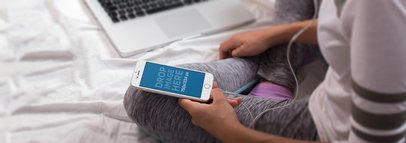 Girl Sitting on her Bed Listening to Music With Her iPhone 6 a14259wide