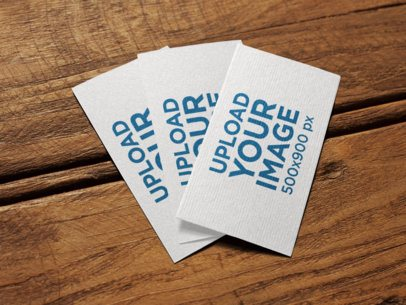 Three Business Cards Mockup Lying on a Wooden Surface a14992