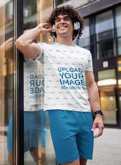 Sublimated T-Shirt Mockup of a Curly-Haired Man Listening to Music in the City 42760-r-el2