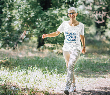 T-Shirt Mockup of a Happy Senior Woman Walking in the Forest 42007-r-el2
