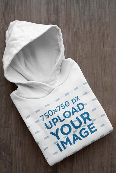 Mockup of a Folded Customizable Hoodie Placed on a Wooden Surface 33874a