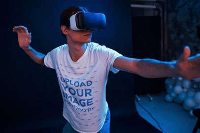 T-Shirt Mockup of a Young Man Playing with a VR in a Dark Room m1913-r-el2