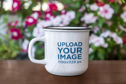 Mockup of a 12 oz Enamel Mug by a Flower Bush m2960-r-el2