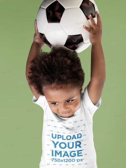 T-Shirt Mockup of a Little Boy Holding a Soccer Ball m3637-r-el2