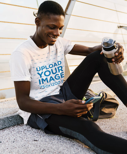 T-Shirt Mockup of a Happy Man Checking His Phone After Training M4347-r-el2