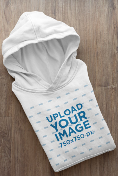Mockup of a Folded Hoodie Placed on a Wooden Surface 33875a