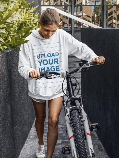 Hoodie Mockup Featuring a Serious Woman Walking With Her Bike m4289-r-el2