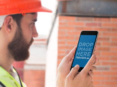 Mockup of a Man Using an iPhone in Portrait Mode Against a Brick Wall 12421