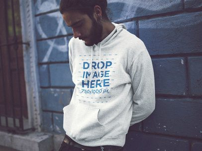 Hoodie Mockup of a Young Hipster Guy Staring Down and Leaning Against a Wall a12594